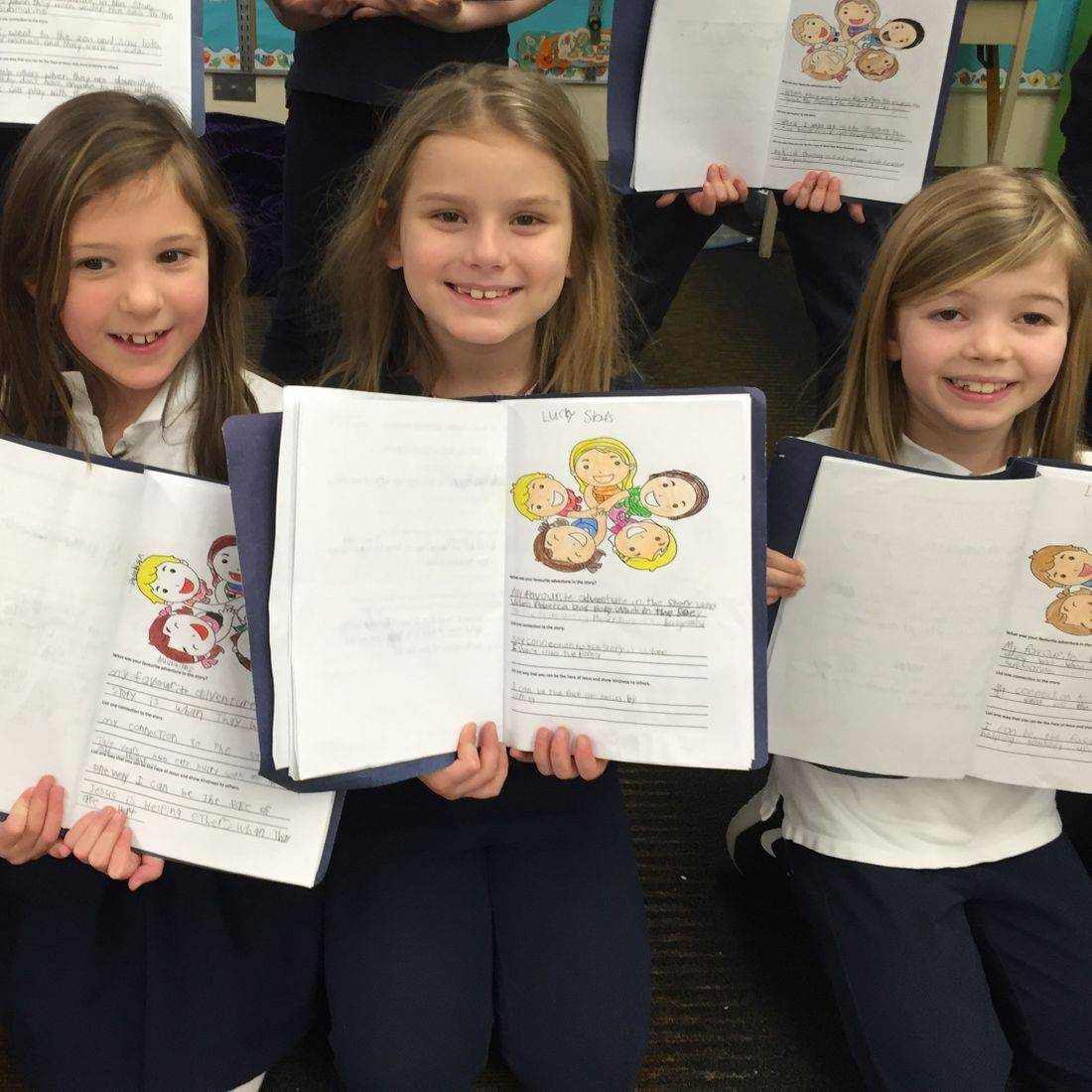 Grade 2 girls proud of their colouring and writing about the book Lucky Stars by Daniella Grsic