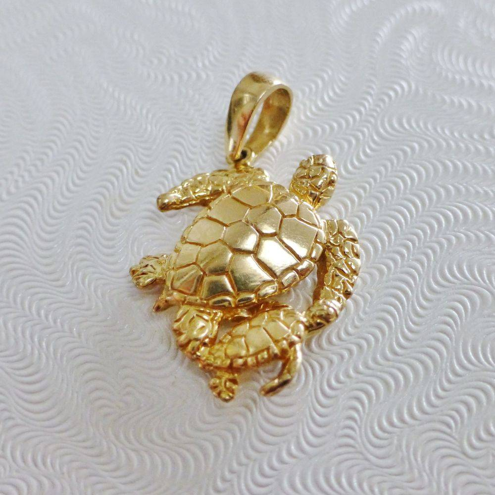 close up picture of a yellow gold mother and child sea turtle charm
