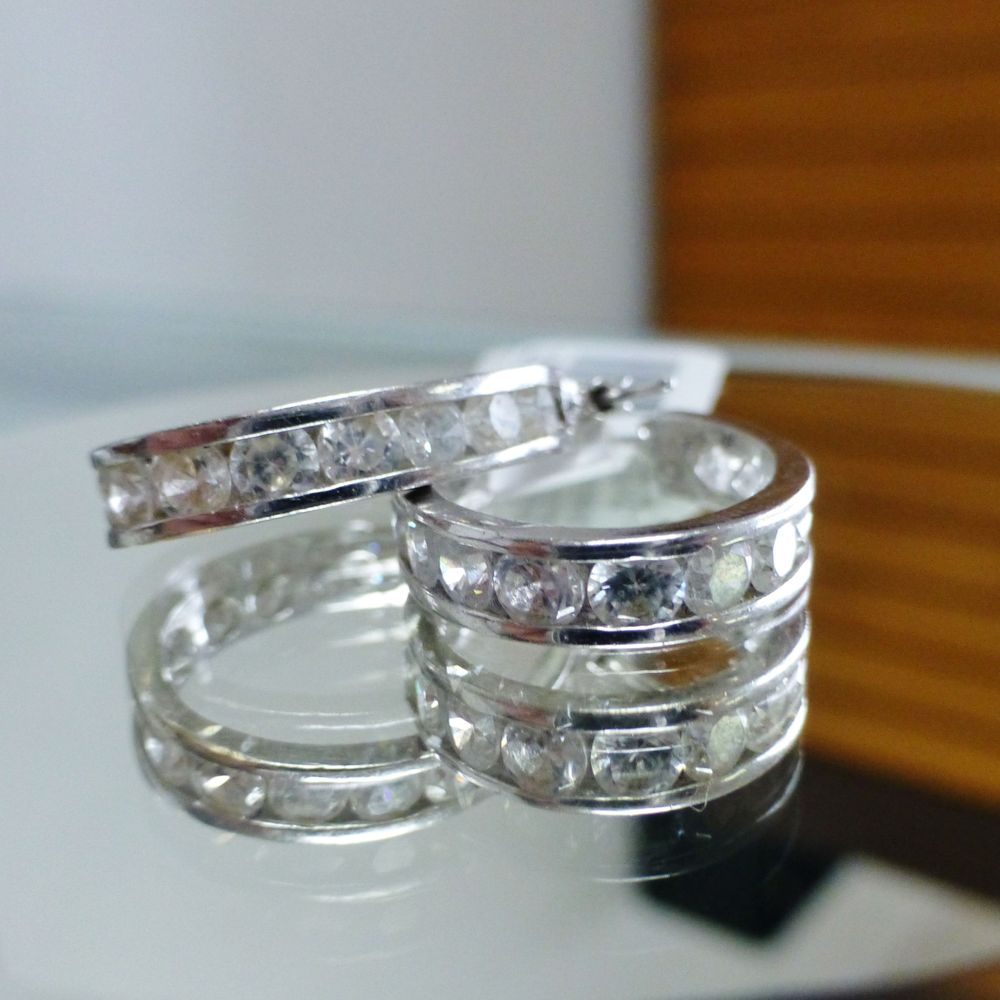 close up picture of a pair of white gold oval hoops with round cut cubic zirconia