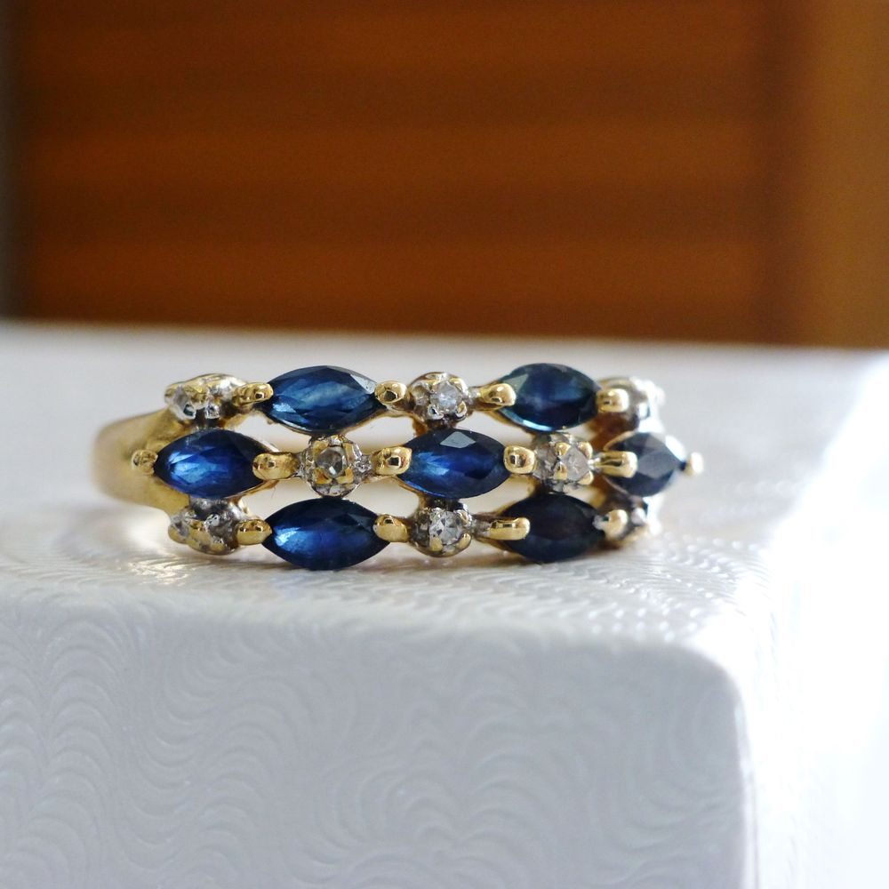 Yellow gold ring with alternating round diamonds and marquise blue sapphires prong set in three row
