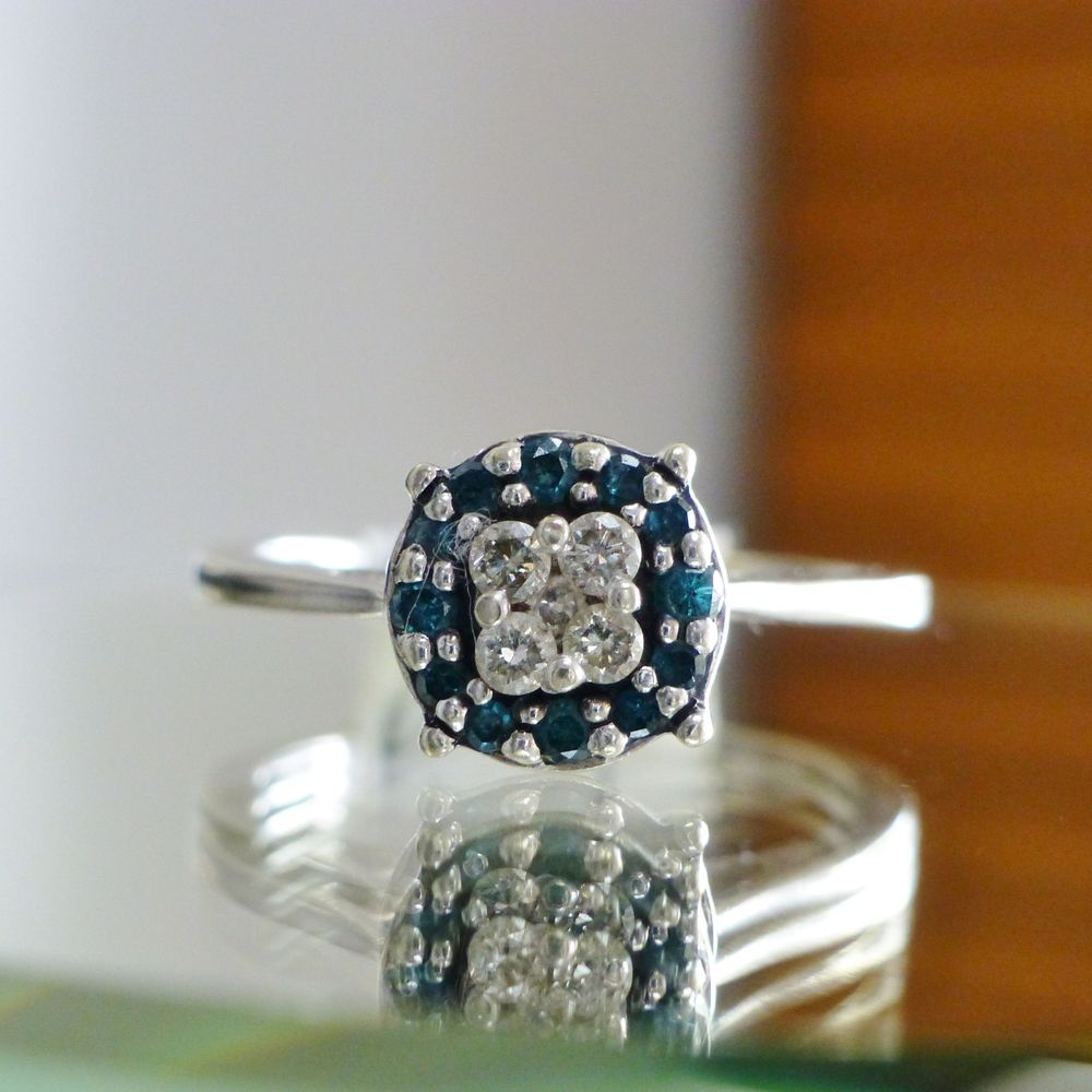 Closeup picture of a white gold blue diamond halo white diamond cluster ring