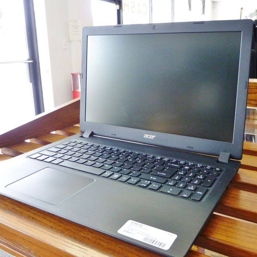 closeup picture of black Acer Aspire laptop on a wooden shelf