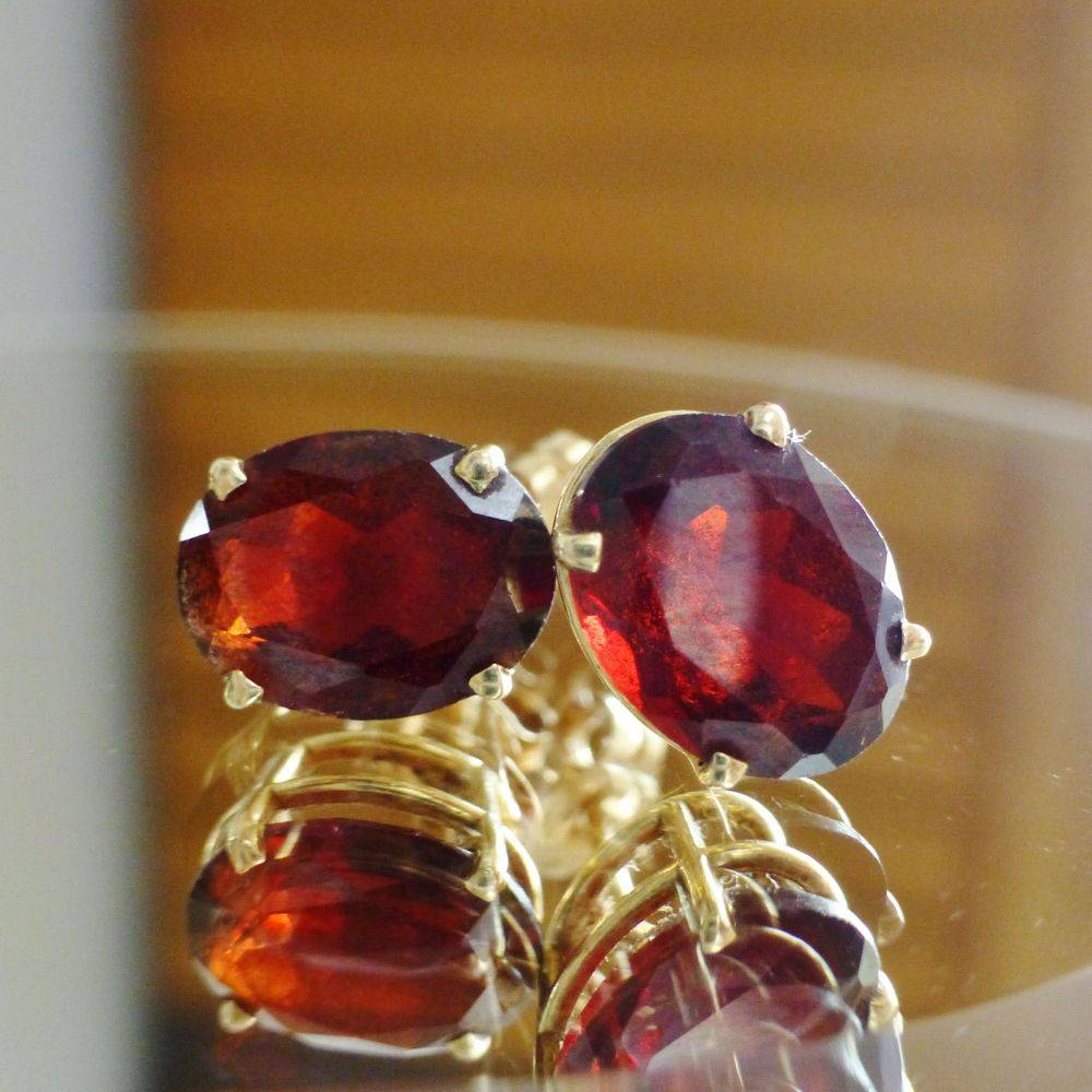 close up picture of a pair of yellow gold, prong set oval cut red garnet earrings