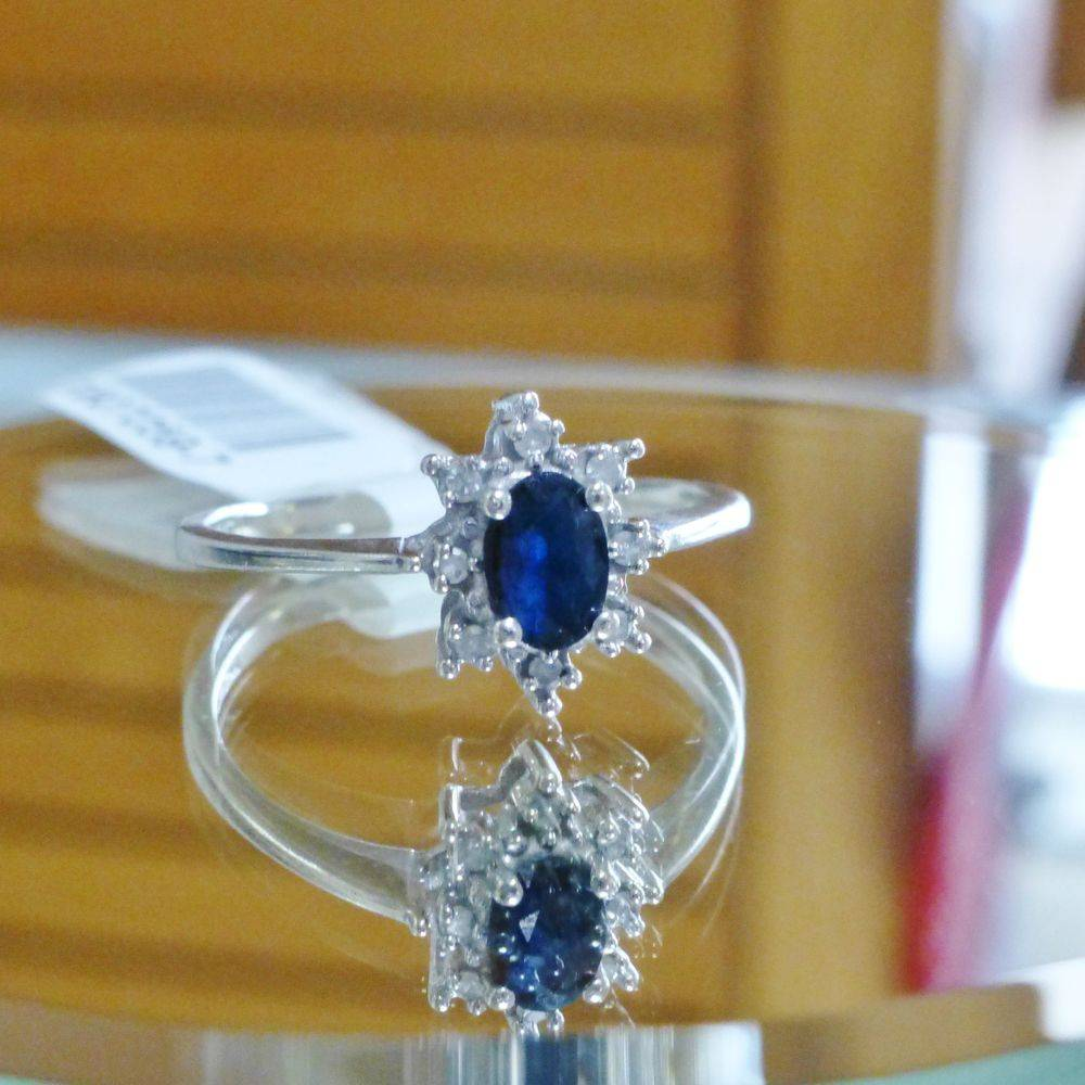 upclose picture of a white gold oval cut blue sapphire with round diamond accents ring