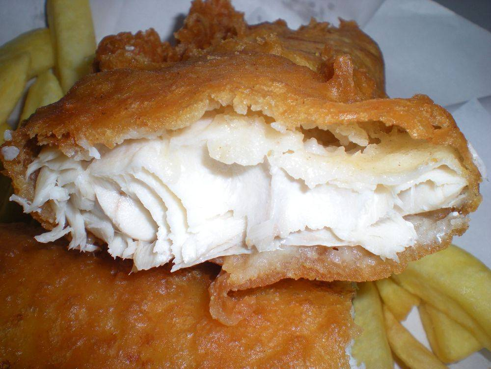 Freshly cooked battered haddock broken in two showing the delicious white flaked fish. cooked fresh from our fish & chips van.