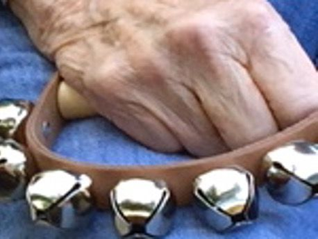 older adult hand playing bells music therapy