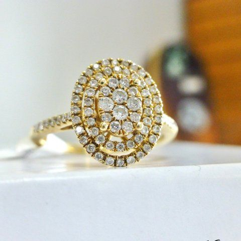 Oval shaped diamond cluster framed by two diamond halos prong set in yellow gold
