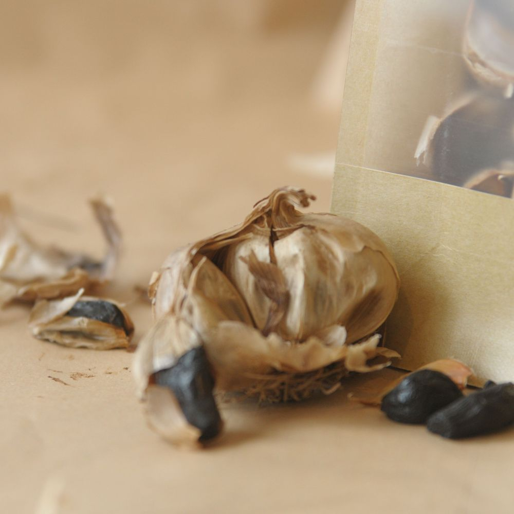 bulb of black garlic on neutral background with exposed, peeled black cloves