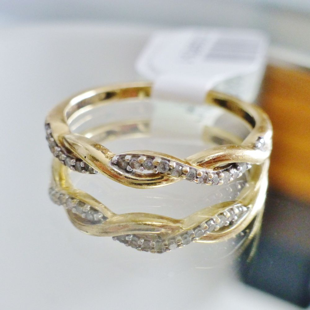 close up picture of a yellow gold diamond infinity twist wedding band