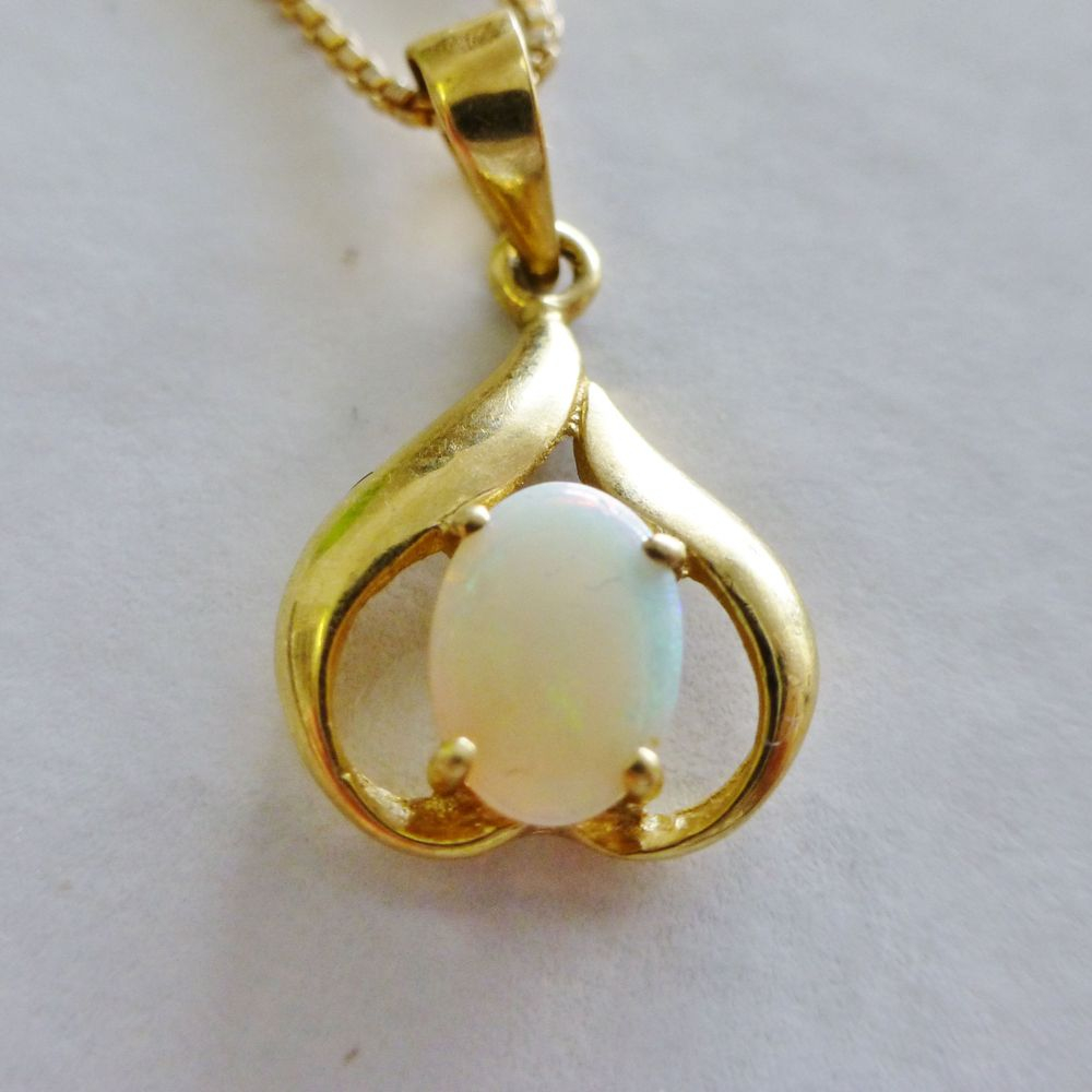 Closeup Picture of an Oval Cut Opal framed by a yellow gold upside down heart charm