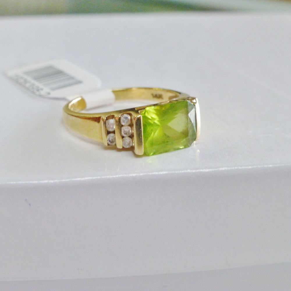 Rectangular Peridot Bar Set from East to West with side diamonds channel set in a yellow gold ring