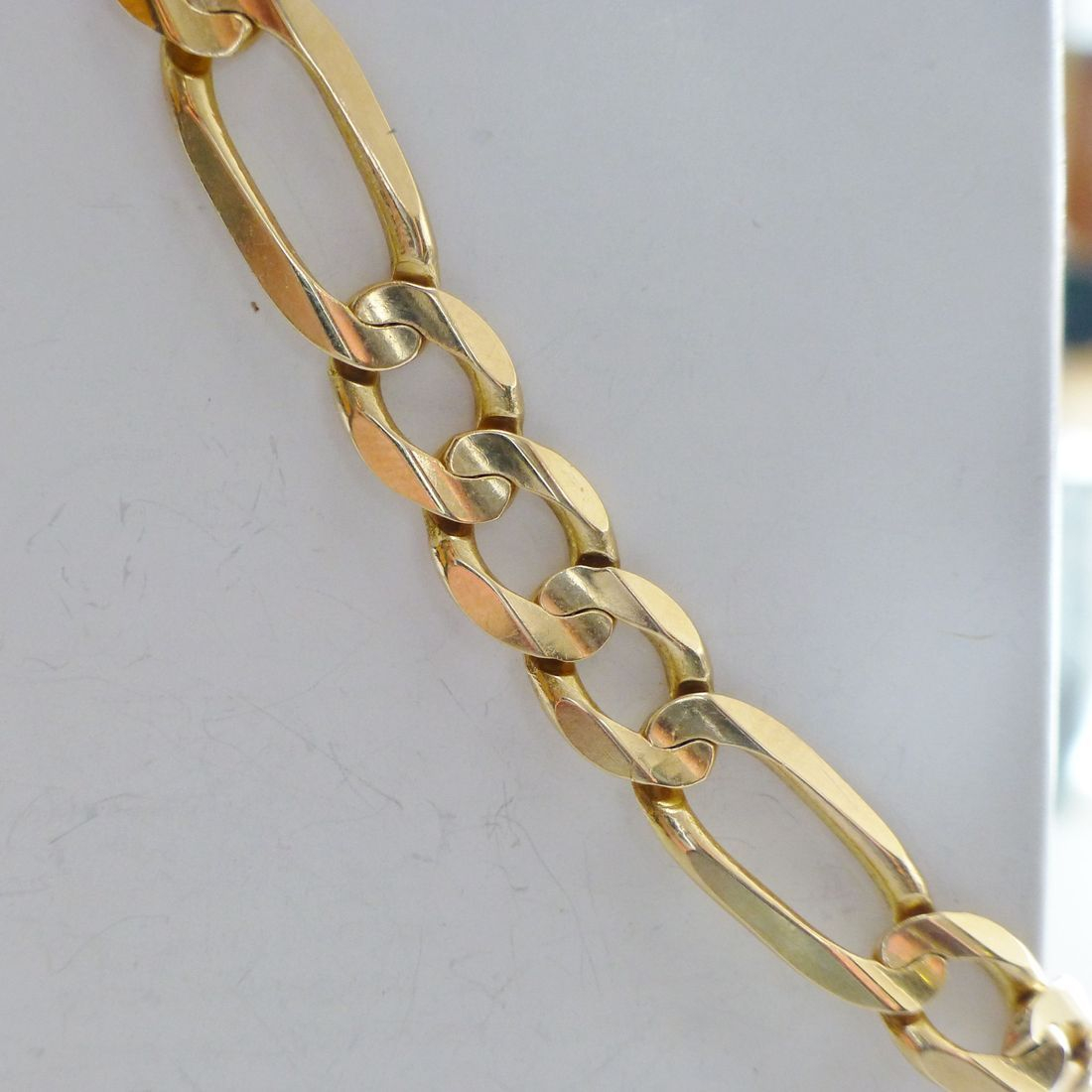 Shiny Yellow Gold Figaro Link Bracelet Hanging Diagonally on A White Box