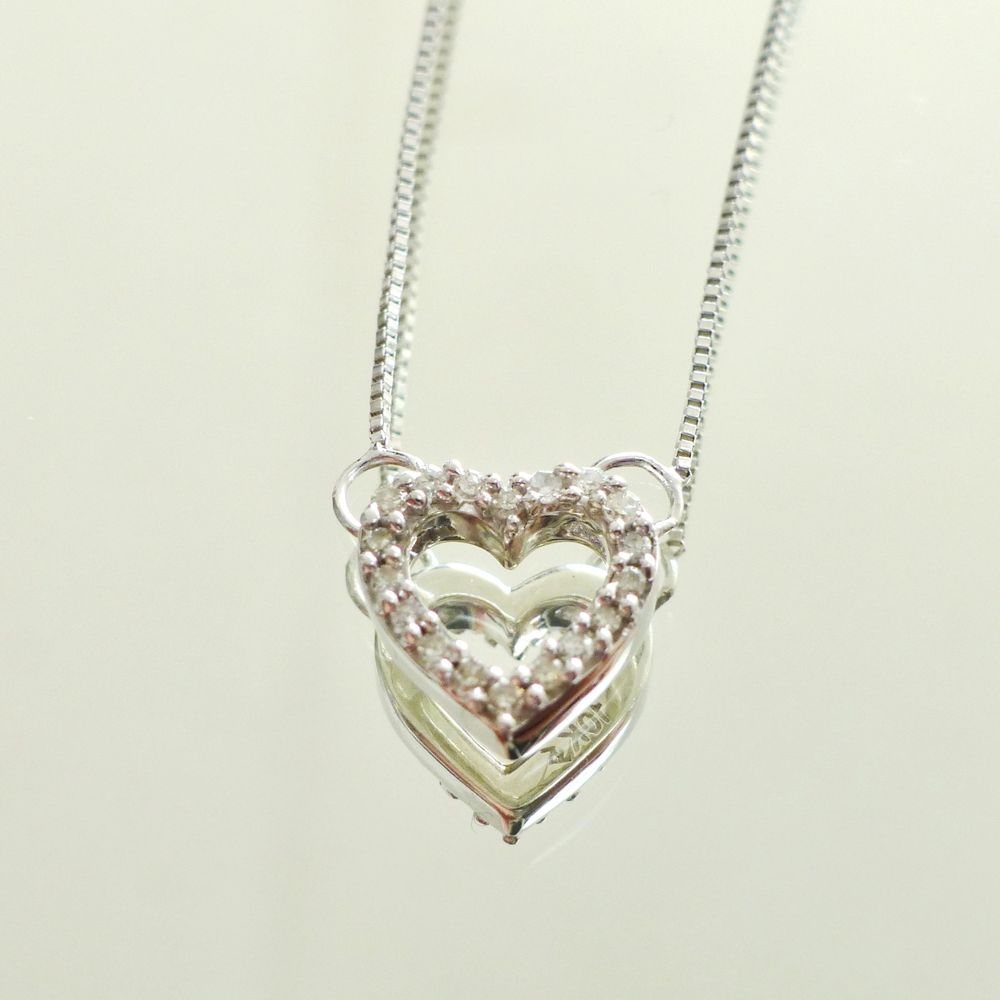 close up picture of a white gold adjustable box link chain with a center station open heart diamond pendant