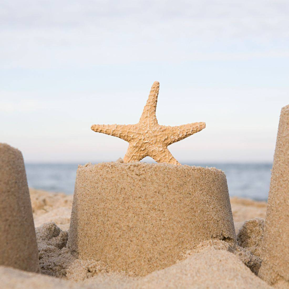 sandcastle with a sand star on a beach