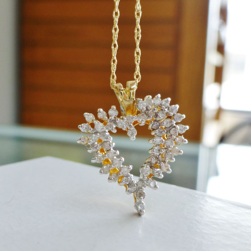 Picture of an open heart diamond cluster charm on a yellow gold necklace