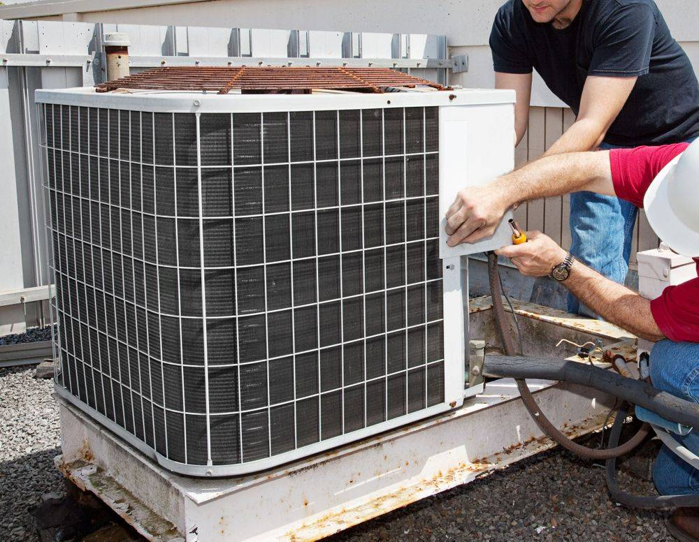 Service technicians repairing an air conditioner unit