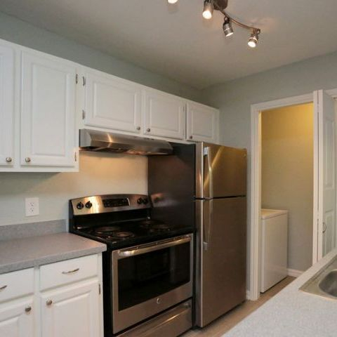 apartment kitchen, stainless steel appliances, white cabinets, track lighting