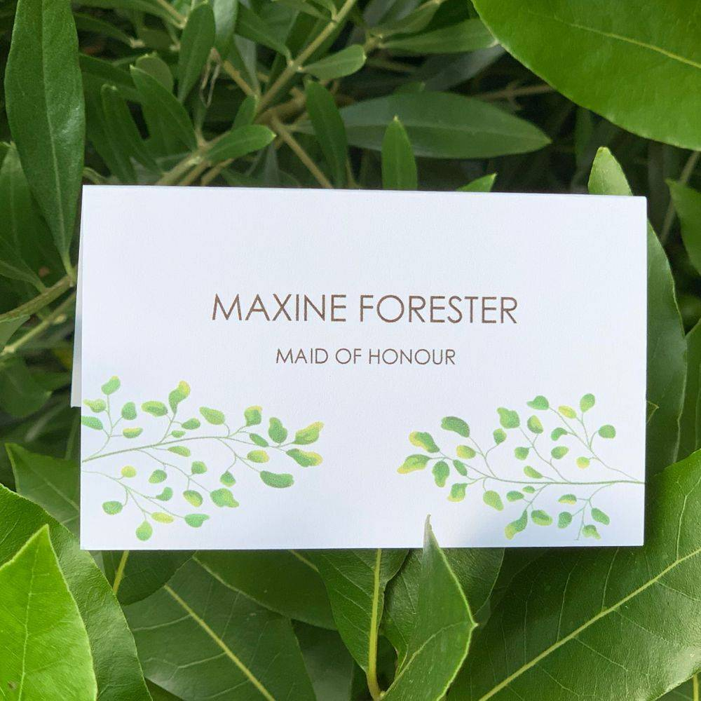 Botanical theme wedding guest place card in white with green leaves