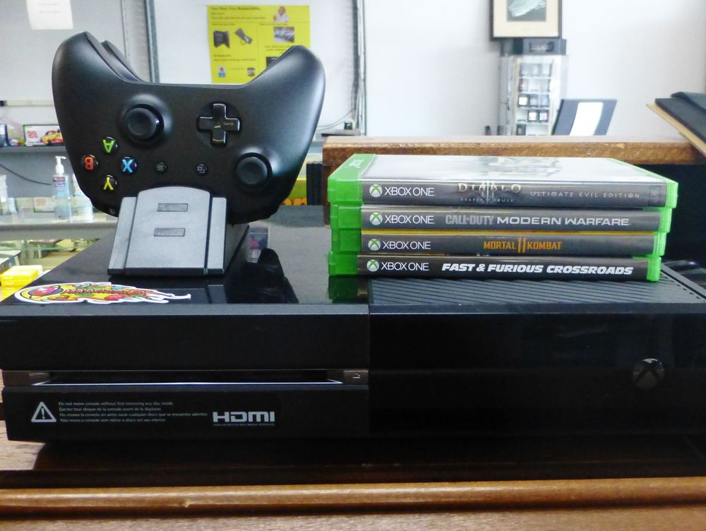 close up picture of a black xbox one system with two controllers and 4 games on top