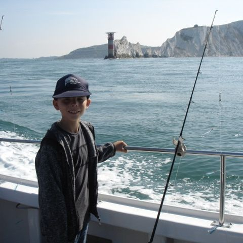 Young boy on boat passing Needles lighthouse