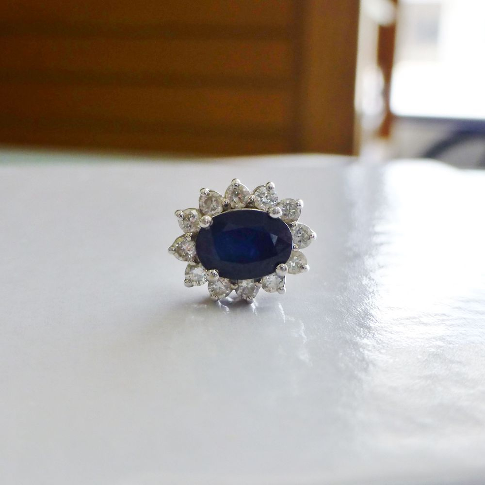Closeup picture of an oval cut blue sapphire diamond halo charm in white gold