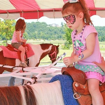 Little girl with face paint riding on a pony carousel ring