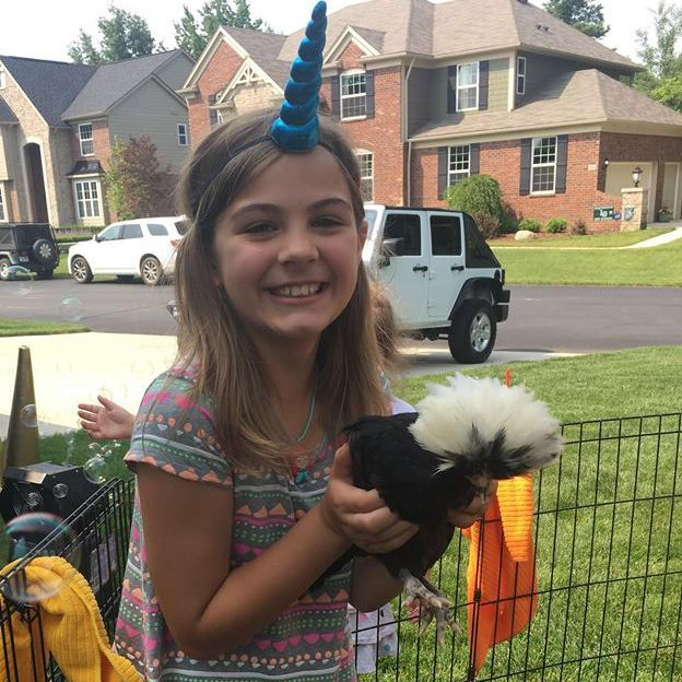 little girl wearing unicorn hat holding chicken