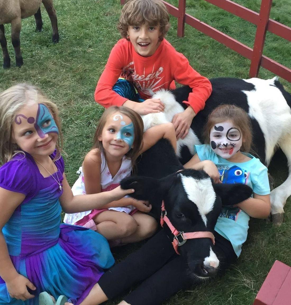 Children sitting around calf