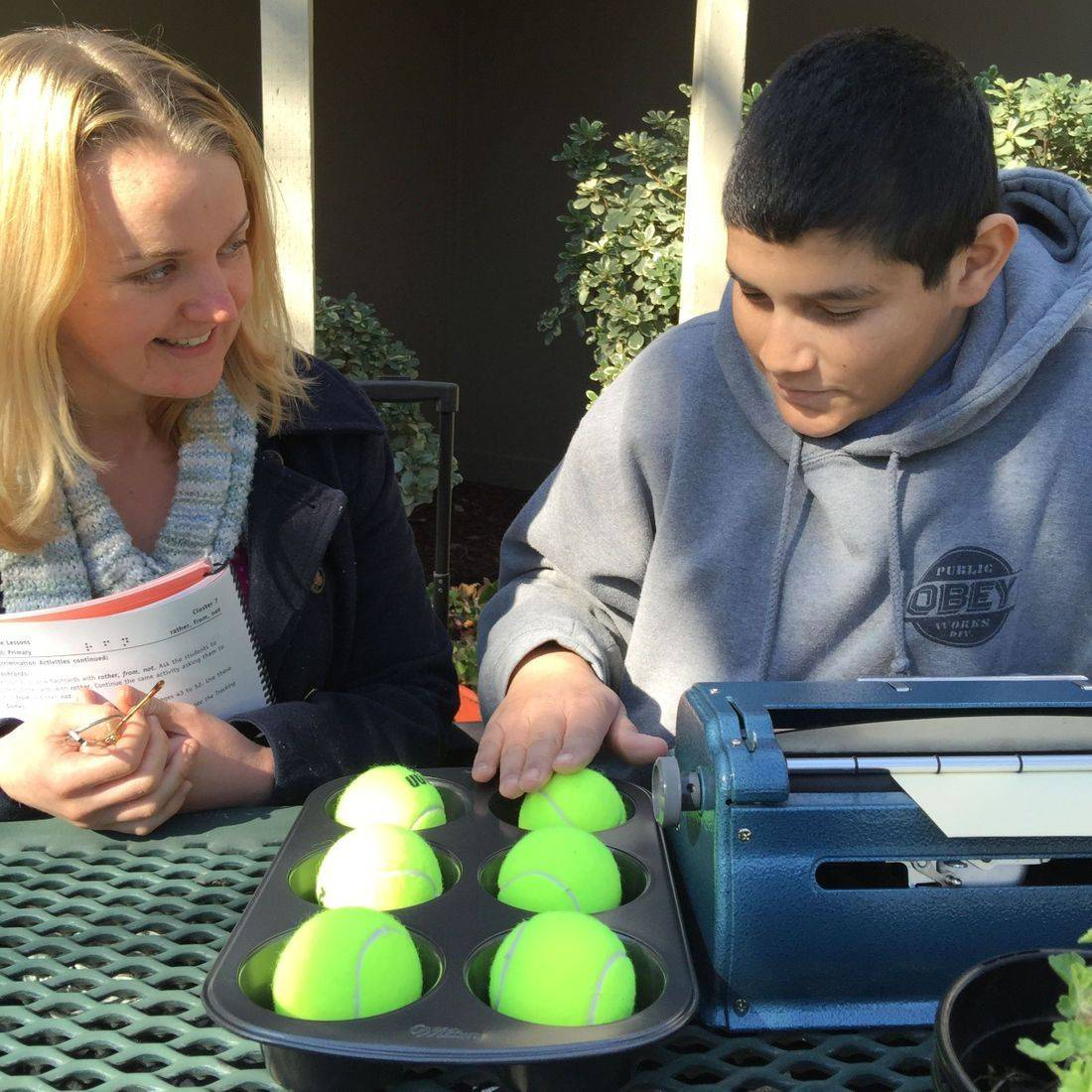 A blind young man is learning braille with his TVI. He is using a braille writer and tennis ball braille cell.