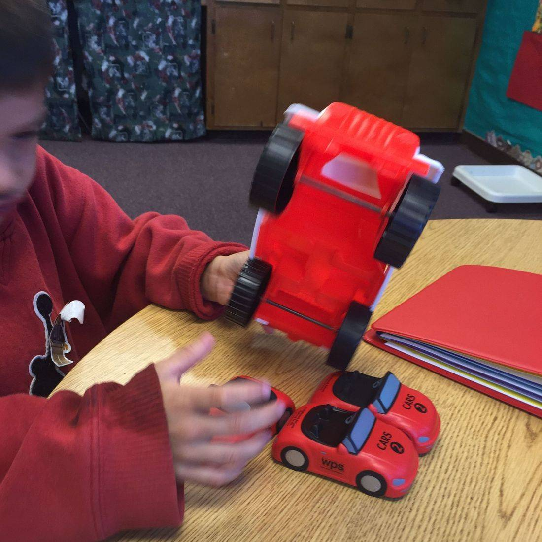 Very young blind student is learning the concept of car by exploring a variety of toy cars. He is holding one in his hand exploring the wheels and axels. He has three more cars on a table in front of him.
